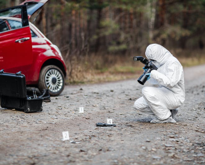 Forensic scientist taking pictures at crime scene. Study Forensic Science abroad.