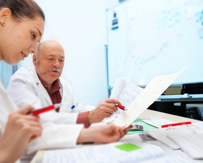 Clinical researchers examining results. Study a Master's in Public Health and become a clinical research coordinator.