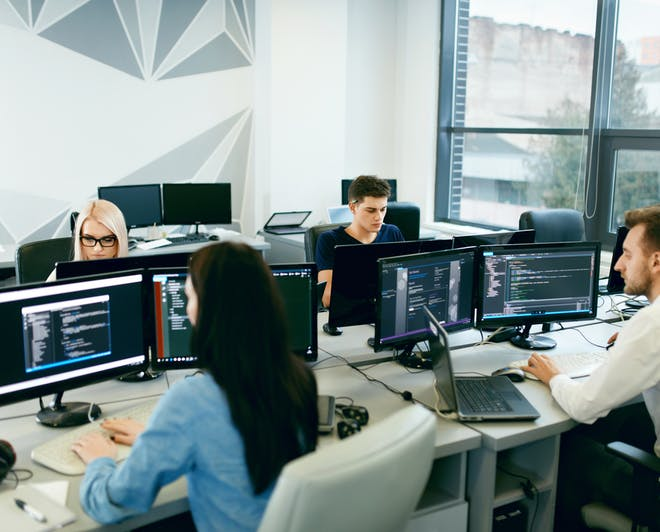 Group of young developers working on their computers in a modern office