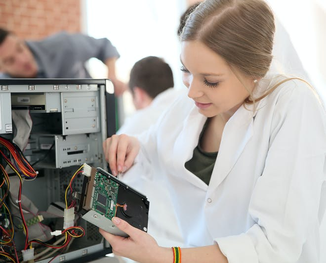 Young female Computer Science student removes the hard drive from a computer case