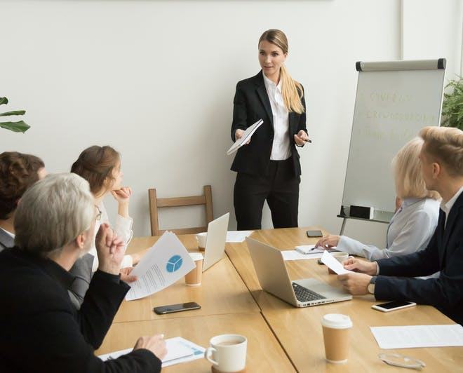 Female staff member speaks in front of her colleagues during a business meeting