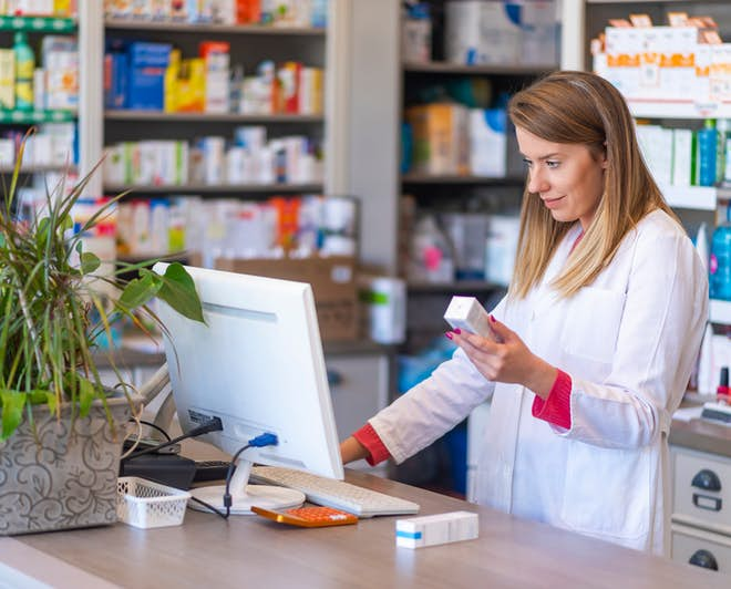 Female pharmacist working in a drug store or pharmacy