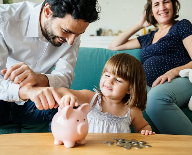 Family teaching young daughter to save money
