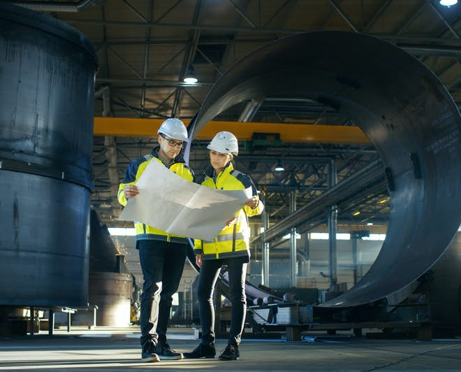 Two industrial engineers look at plans