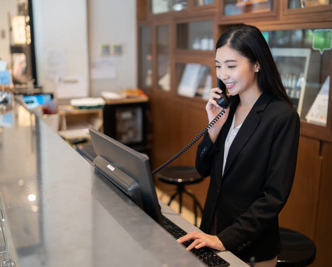 Female hotel receptionist talking on the phone