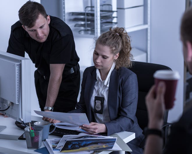 Female police detective examines a document with her colleague