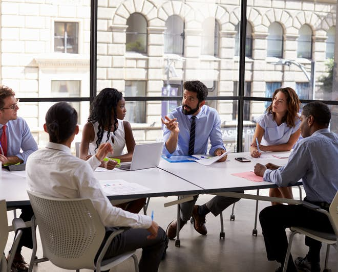 Group of people sitting at a table and talking during a business meeting